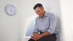 Hispanic business man texting in office Stock Footage