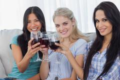 Happy friends toasting with red wine together and looking at camera Stock Photos