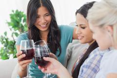 Stock Photo of Cheerful friends having red wine together