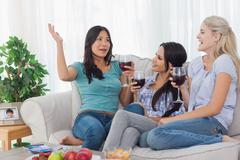 Cheerful friends having red wine together and talking - stock photo