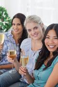 Happy friends enjoying white wine together looking at camera - stock photo