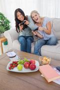 Stock Photo of Happy friends playing video games and laughing