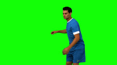 Football player kicking a football on green screen Stock Footage