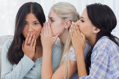 Two friends whispering secrets to surprised brunette Stock Photos