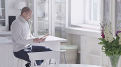 Handsome young man relaxing with a newspaper in his light and elegant home - stock footage