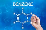 Stock Photo of hand with pen drawing the chemical formula of benzene