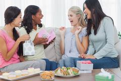 Friends offering gifts to woman during party - stock photo
