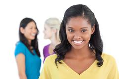 Smiling dark woman looking at camera with two women behind her Stock Photos