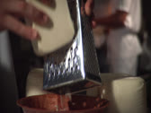 Stock Video Footage of Grating cheese, with cook bg, static -alt