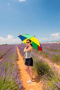 lavander field, provence. beautiful woman with colourful umbrella - stock photo