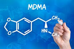 hand with pen drawing the chemical formula of mdma - stock photo