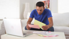Hispanic man stressed while paying bills Stock Footage