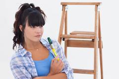 Woman holding paintbrush - stock photo