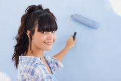 Pretty woman painting wall blue and smiling at camera - stock photo