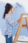 Stock Photo of Woman using paint roller to paint wall blue