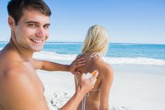 Man putting sun cream on girlfriends back smiling at camera - stock photo