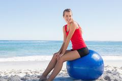 Athletic young woman sitting on exercise ball looking at camera Stock Photos