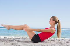 Fit blonde doing pilates core exercise - stock photo