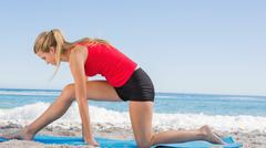 Stock Photo of Fit blonde stretching leg on exercise mat