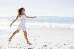 Stock Photo of Happy brunette in white sun dress skipping on the sand