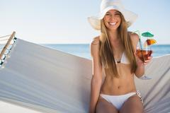 Stock Photo of Happy blonde wearing bikini and sunhat sitting on hammock with cocktail