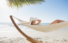 Stock Photo of Woman wearing sunhat and bikini relaxing on hammock