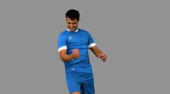 Cheerful football player gesturing on grey screen Stock Footage