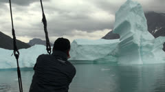 A man in a boat looks at an iceberg in a Greenland ice fjord slow  Stock Footage