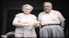 252 - grandparents pose for camera outside their home - vintage film home movie Stock Footage