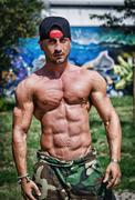 Shirtless bodybuilder showing torso muscles, abs, pecs and arms outdoors Stock Photos