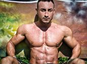 Handsome, muscular bodybuilder sitting against colorful wall Stock Photos