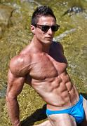young muscle man outdoors in water showing muscular abs, pecs and arms - stock photo