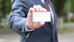 Businessman showing blank business card outdoors in a park Stock Footage