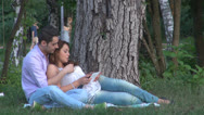 Stock Video Footage of Young couple are relaxes in the park ,using touchscreen tablet