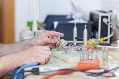 Dental technician with drill in laboratory Stock Photos