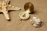 Stock Photo of compass and starfish on a sandy beach