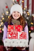 Pretty girl with an armful of christmas gifts Stock Photos
