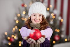 Cute young girl holding out a Christmas bauble - stock photo