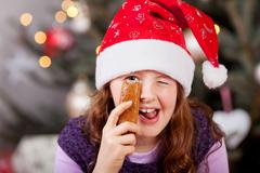 Girl in a Santa hat giving a joyful wink Stock Photos