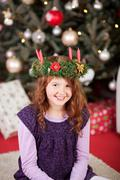 Smiling girl wearing an Xmas candle wreath - stock photo