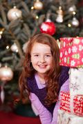 Pretty girl peering around christmas presents Stock Photos