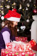 little girl unwrapping christmas gifts - stock photo