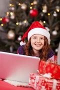 beautiful young girl wearing a red santa hat - stock photo