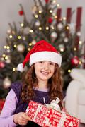 Beautiful laughing girl in a Santa hat - stock photo