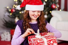 Young girl unwrapping her christmas present Stock Photos