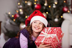 little girl holding her christmas gift - stock photo