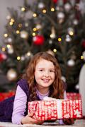 Joyful little girl with a christmas gift Stock Photos