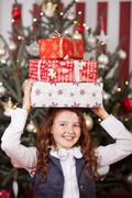Laughing girl with christmas gifts on her head Stock Photos