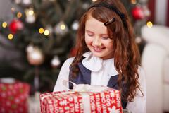 happy little girl holding a christmas present - stock photo