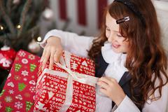 Excited little girl undoing her christmas present Stock Photos